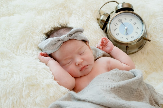 Dreaming newborn baby girl naked on fur blanket with clock