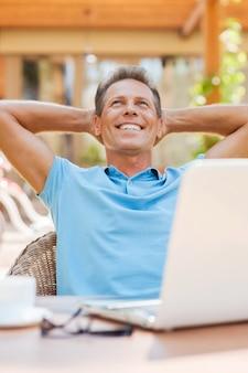 Мечтает об отпуске. расслабленный зрелый мужчина держится за руки за головой и улыбается, сидя за столом на открытом воздухе с ноутбуком на нем