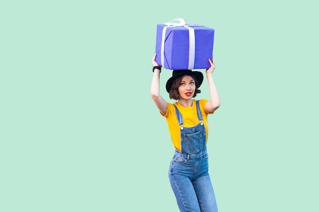 힙스터를 입은 긍정적인 어린 소녀는 데님 작업복을 입고 검은 모자를 쓰고 머리 아래에 서서 숙고하는 얼굴로 거대한 크고 무거운 선물 상자를 들고 있습니다. 스튜디오 촬영, 녹색 배경, 절연
