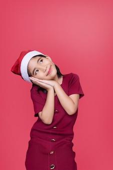 Мечтая девушка санта смотрит вверх, чтобы скопировать пространство на красной изолированной стене