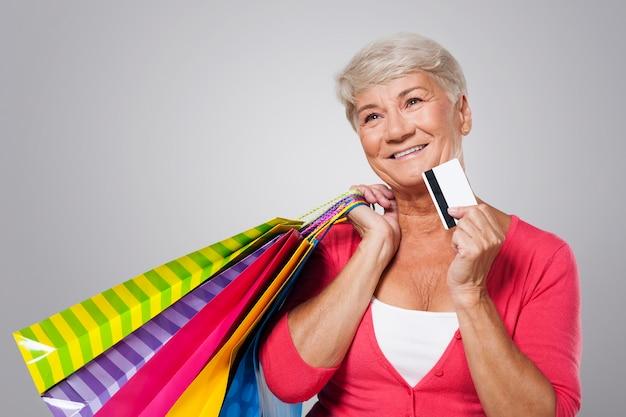 ショッピングバッグとクレジットカードで夢見る年配の女性