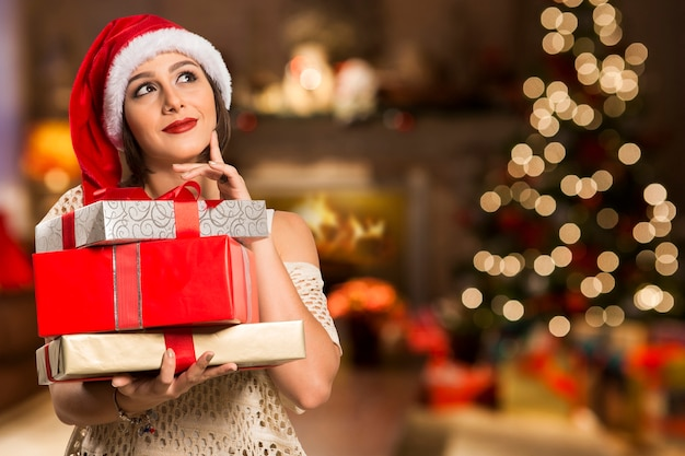 Dreaming thinking happy pensive beautyful woman in red  hat santa claus / gifts, christmas, x-mas concept