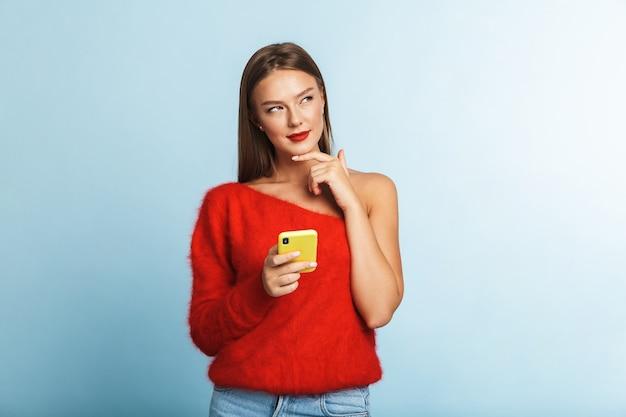 휴대 전화를 사용 하여 격리 된 포즈를 꿈꾸는 생각 젊은 여자.