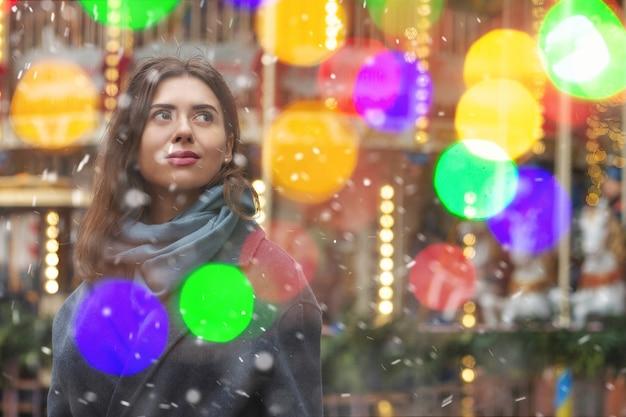 夢見る女性は、降雪時にボケの光で通りを歩いている灰色のコートを着ています。空きスペース