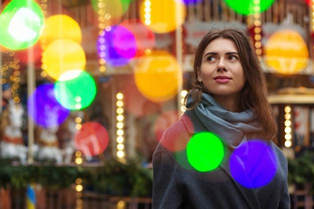 夢を見ている女性は、ボケの光で通りを歩いている灰色のコートを着ています。空きスペース