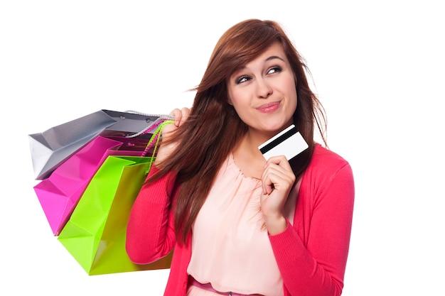 Мечтающая женщина с хозяйственными сумками и кредитной картой