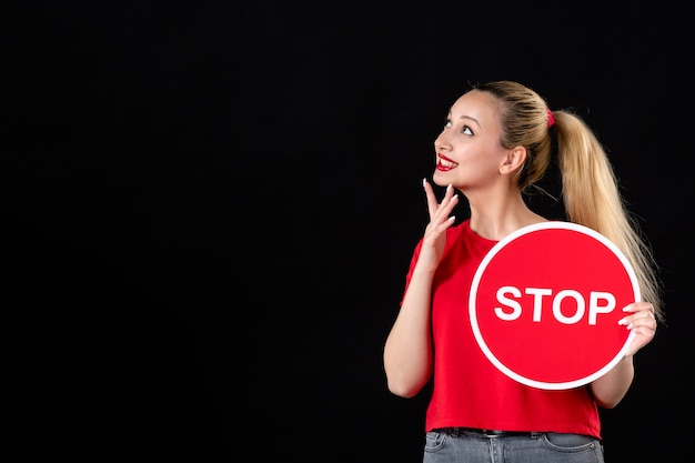 Dreaming young female holding red stop sign on black