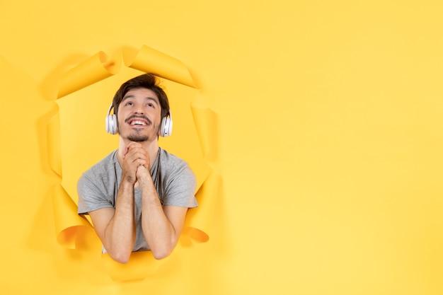 노란색 배경 오디오 초음파 소리에 헤드폰으로 음악을 듣고 꿈꾸는 젊은 남성