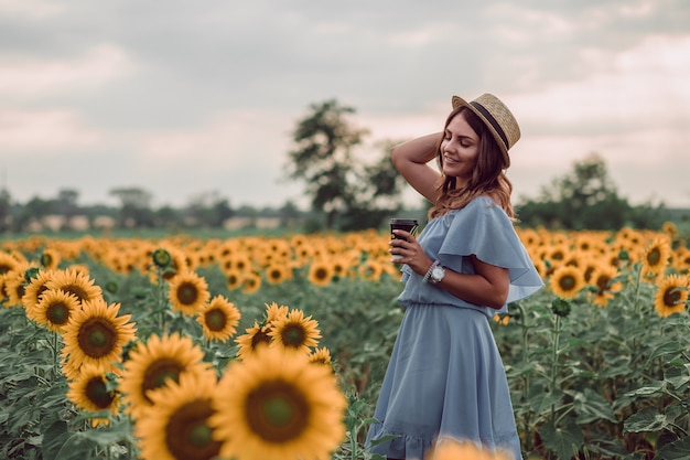 Dreaming young woman in blue dress and hat holding a cup of coffee in a field of sunflowers at summer, view from her side. looking to the side. copy space