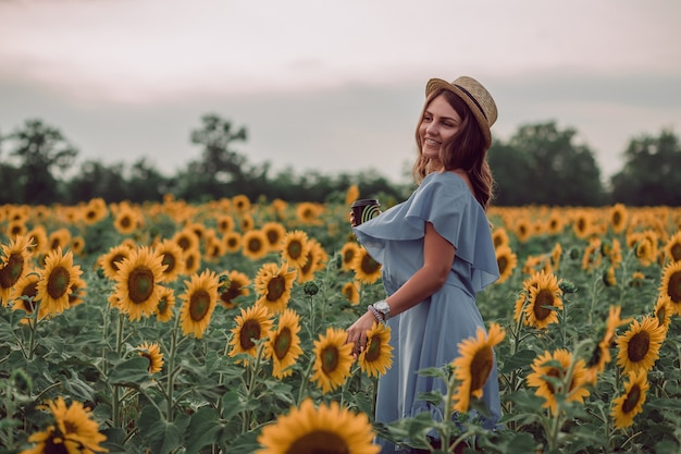 Dreaming young woman in blue dress and hat holding a cup of coffee in a field of sunflowers at summer, view from her side. looking to the side. smiling. copy space