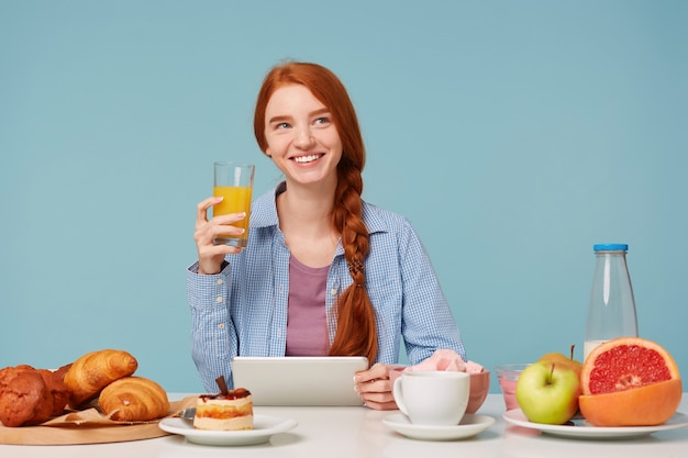 Dreamingly looking to the upper right corner, beautiful smiling red-haired woman drinking orange juice