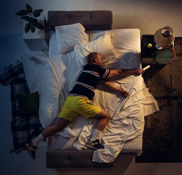 Сказочный вид сверху молодого профессионального теннисиста, спящего в своей спальне в спортивной одежде