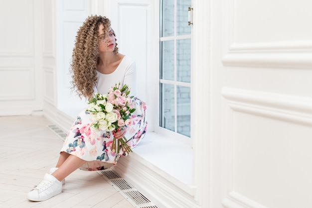 Dreamly romantic woman  holding a flowers bouquet and  looking  in the window sitting in the white room- image