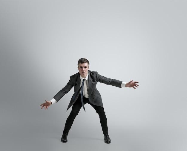 큰 가능성에 대한 꿈. 사무실에서 남자는 회색 벽에 골키퍼처럼 축구 또는 축구에서 훈련합니다. 모션, 행동에 사업가에 대한 특이한 모습. 스포츠, 건강한 라이프 스타일.