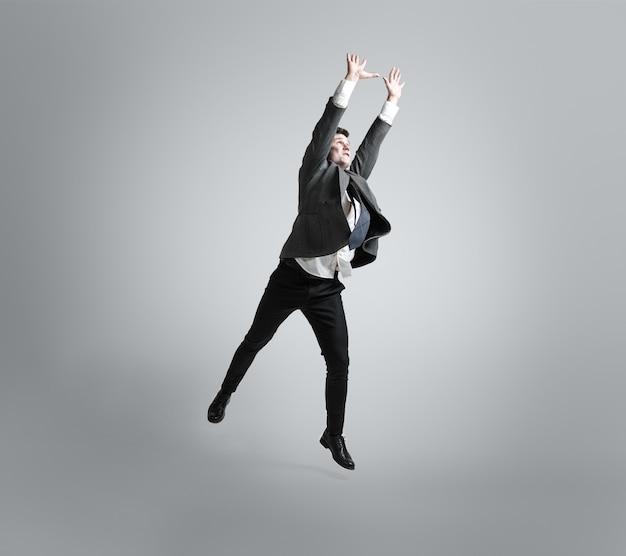 Sogna grandi possibilità. l'uomo in abiti da ufficio si allena nel calcio o nel calcio come il portiere sul muro grigio. look insolito per uomo d'affari in movimento, azione. sport, stile di vita sano.