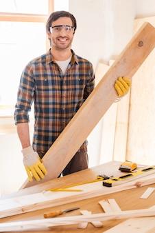 내 작업실에서 꿈이 탄생합니다. 자신의 작업장에 서서 나무 판자를 들고 웃고 있는 자신감 있는 젊은 남성 목수
