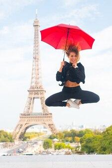 夢が叶うコンセプト。パリ市内中心部でスポーティでアクティブな女性観光客が飛び上がります。女の子の観光客は散歩や観光を楽しんでいます。空の背景、エッフェル塔を訪問することに興奮している傘を持つ女性。