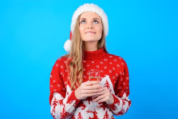 크리스마스에 꿈이 이루어집니다! 긴 금발 머리 입술을 물고 밝은 파란색 배경에 고립 된 소원을 만드는 행복 흥분된 쾌활한 즐거운 꿈꾸는 소녀의 초상화