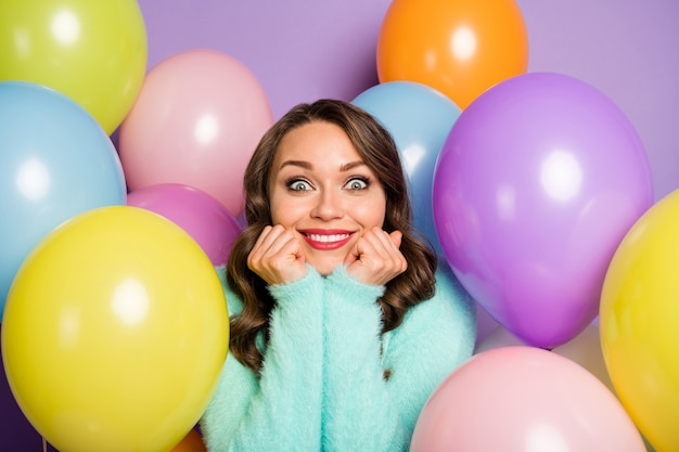 Dreams come true! portrait of pretty lady hands on cheeks surrounded many colorful air balloons birthday party surprise wear fuzzy pastel sweater.