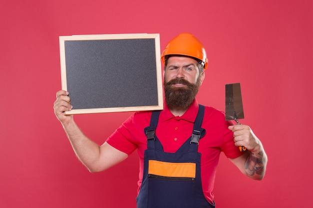 꿈은 이루어진다. 숙련된 미장공. 성공적인 리노베이션. 석고 도구와 수염된 남자 노동자입니다. 하드 모자에 석고 힙스터 빌더는 칠판 복사 공간을 보유합니다. 전문 미장공.