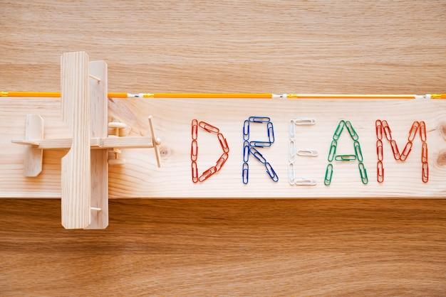 꿈은 이루어진다. 화려한 스테이플과 나뭇결 위에 놓인 나무 비행기로 만든 텍스트의 상위 뷰