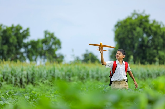 Dreams of flight! indian child playing with toy airplane at green field