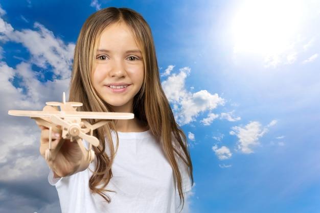 Мечтает о полете! ребенок играет с игрушечным самолетиком
