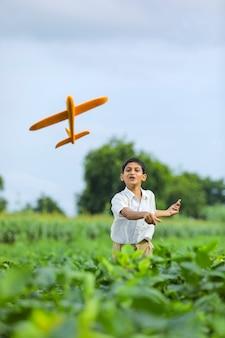 Мечты о полете! индийский ребенок играет с игрушечным самолетиком на зеленом поле