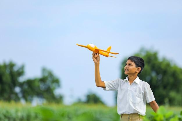 비행의 꿈! 그린 필드에서 장난감 비행기를 가지고 노는 인도 아이