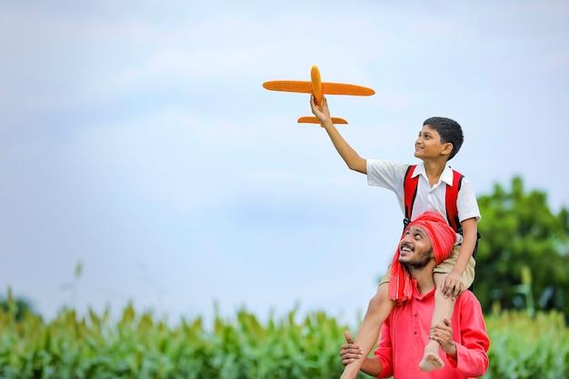 비행의 꿈! 사이클에 그의 아버지와 장난감 비행기를 가지고 노는 인도 아이
