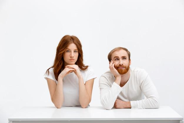 Мечтательный взрослый мужчина и серьезная рыжая женщина