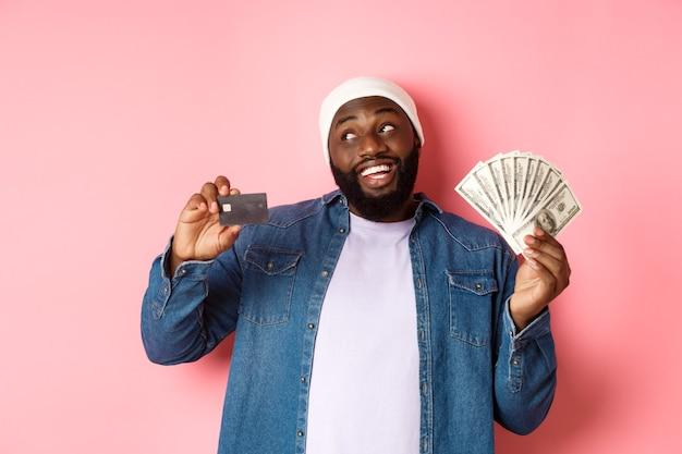 Uomo afroamericano sognante che mostra carta di credito e dollari, pensando allo shopping e sorridendo, in piedi su sfondo rosa