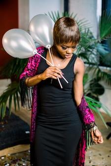 Мечтательная африканская девушка в черном платье празднует, делая желание, держа бокал шампанского, воздушные шары. женский день, с новым годом концепция макета