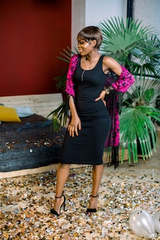 Мечтательная африканская девушка в черном платье празднует, делая желание. женский день, с новым годом концепция макета