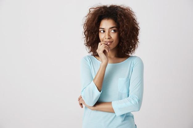 Мечтательная африканская девушка мышления улыбается. белая стена. копировать пространство