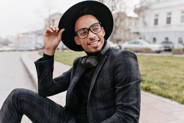 目をそらしている灰色のウールのスーツの夢のようなアフリカの男性モデル。屋外の写真撮影を楽しんでいる大きな帽子と眼鏡の恍惚とした若い男。 無料写真