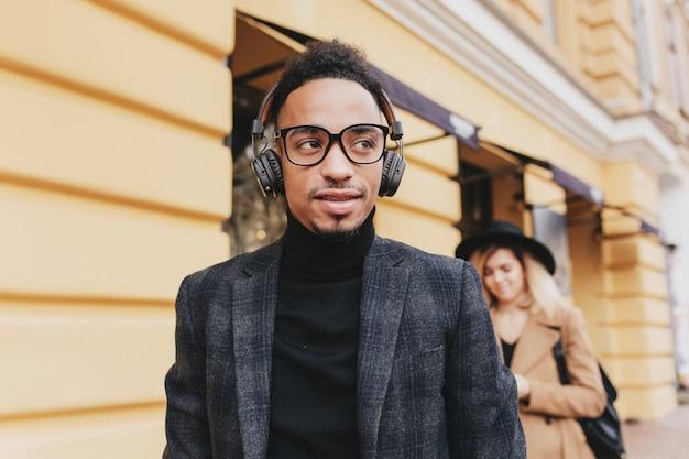 거리에 서있는 안경에 꿈꾸는 아프리카 남자. 헤드폰에서 세련 된 흑인 남자 듣는 음악의 야외 사진.