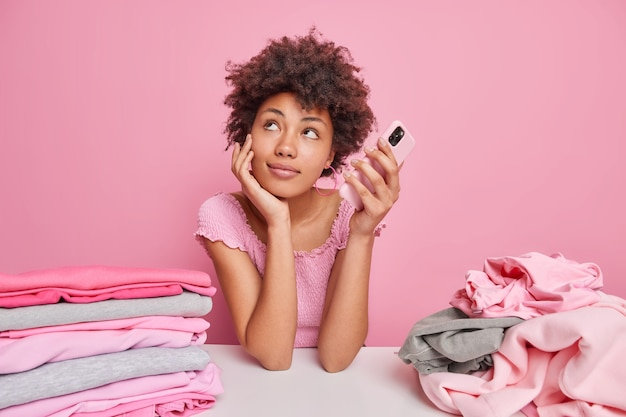 Dreamy afro american woman folds clean clothes after laundry leans at white table holds mobile phone waits for call looks thoughtfully aside poses against pink wall stacks of clothing around