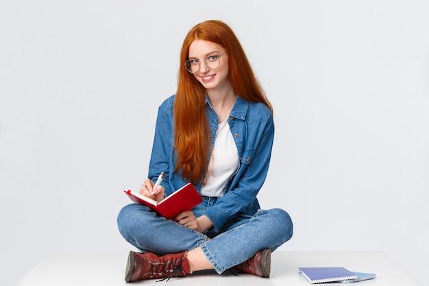 夢のような創造的で才能のある女性作家、学生はジャーナリストになりたい、メモを取り、やることリストを書き、ノートに何かを書き、生意気なカメラを見て、微笑みます。
