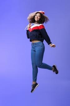 冬のビーニージーンズとスウェットシャツの巻き毛の夢のような女性らしいかわいい女の子が青を飛び越えて...