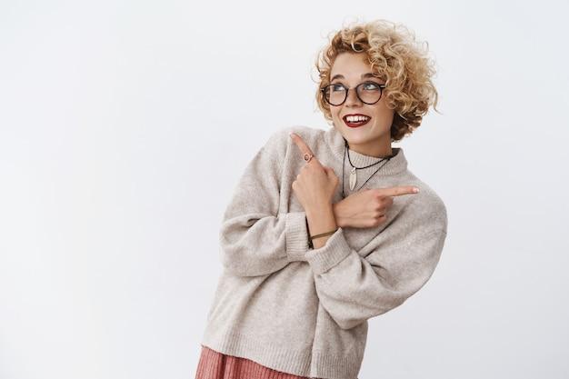 꿈꾸고 어리석은 귀여운 유럽 금발 여성이 다양한 멋진 제품 중에서 선택을 하며 흰색 벽 위에서 행복하게 결정을 내리며 활짝 웃고 있습니다.