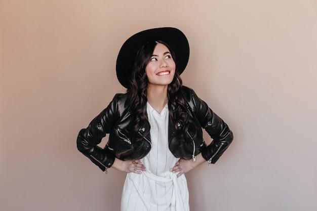 腕を腰に当てて立っている革のジャケットの夢のようなアジアの女性。腰に手を当ててポーズをとる帽子の面白い中国人女性。