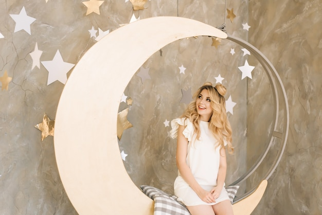 Мечтательная привлекательная блондинка катается на луне. концепция праздника и рождества