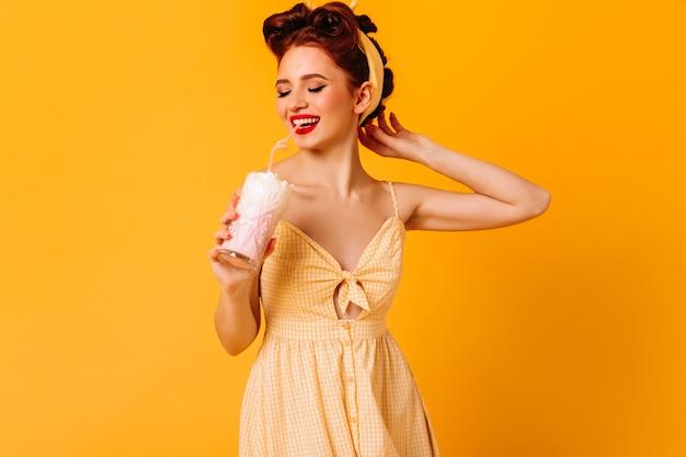 Ragazza attraente vaga che beve milkshake. donna romantica dello zenzero che gode della bevanda sullo spazio giallo.
