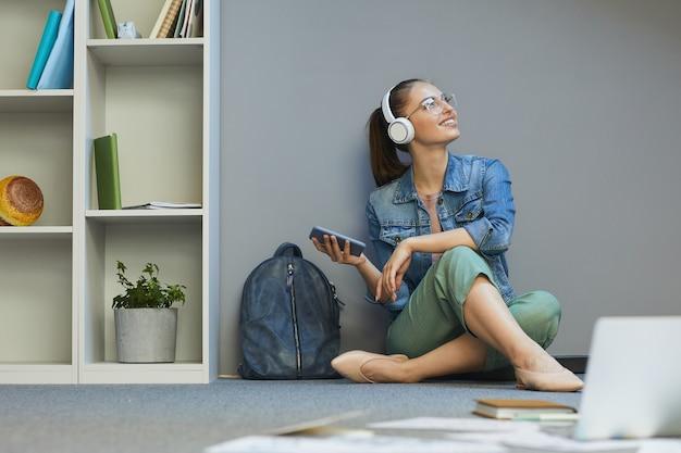 Мечтательная привлекательная девушка-студент сидит на полу и использует смартфон, наслаждаясь музыкой в наушниках