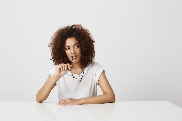 Мечтательная красивая африканская девушка держит очки, думая над белой стеной копирование пространства.
