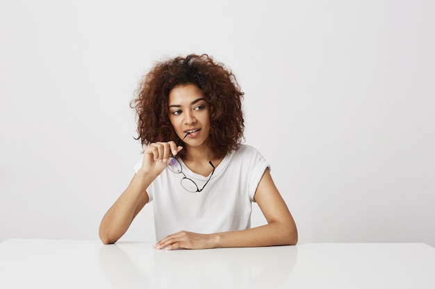 Dreamy beautiful african girl holding glasses thinking over white wall. copy space.