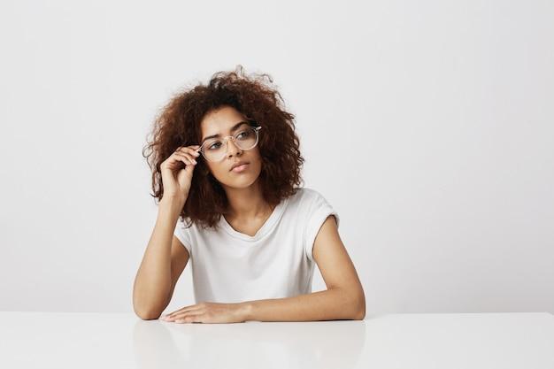 Мечтательная красивая африканская девушка в очках, продумывая белую стену копирование пространства.