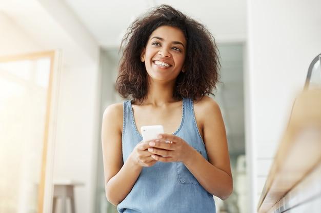 Мечтательная красивая африканская женщина улыбается мышления мечтать, держа телефон, сидя в кафе.