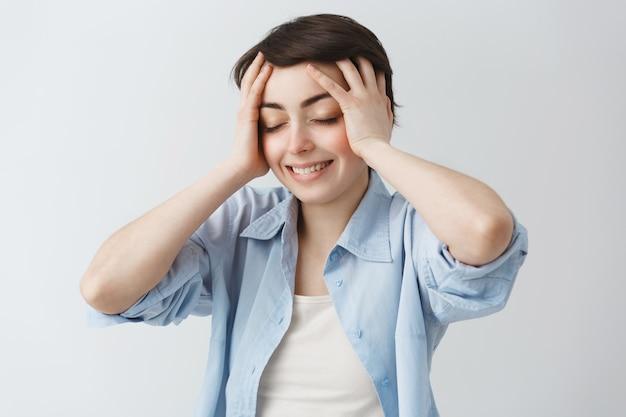 La bella ragazza sognante chiude gli occhi e tocca la testa sollevata, si sbarazzò del mal di testa